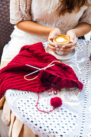 I can create anywhere. Woman knitting on terrace with a cup of coffee. Archivio Fotografico