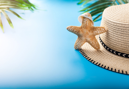 Summer holiday background. Beach accessories: starfish, tropical palm leaves, straw hat on blue background. Vacation and travel items. Summer concept. Front view.
