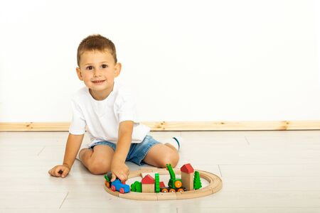 child boy playing with toys indoors at home looking at camera