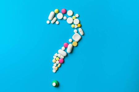 Pills In The Shape Of A Question Mark Over White Background Reklamní fotografie