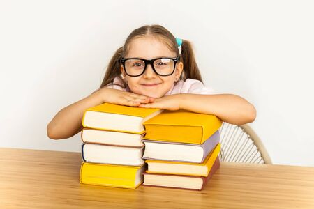 education and school concept - smiling little student girl with sunglasses with many books at school