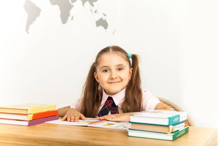 Six years old child reading a book at home, reflects on lessons. Girl studying at table on white background