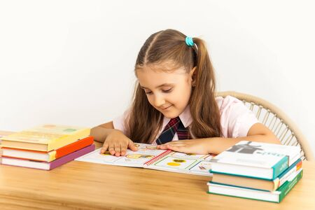 Six years old child reading a book at home, reflects on lessons. Girl studing at table on white background