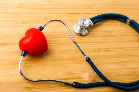 Stethoscope and red heart on wooden table. Cardiology concept