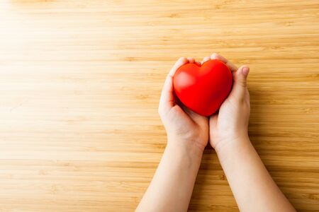 Health care, donate, medicine and charity concept - close up of child's hands holding red heart Фото со стока - 131389755
