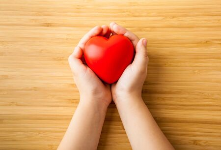 Health care, donate, medicine and charity concept - close up of childs hands holding red heart