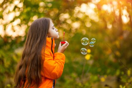 Caucasian child girl blowing soap bubbles outdoor at sunset - happy carefree childhood