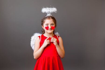 A little Cupid girl in a red dress with wings and halo holding red hearts in her hands, closes her eyes and smiling on a grey background. Valentines Day, Mothers Day, International Womens day