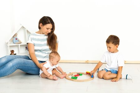 Motherhood. Spending time together. Mother Sitting With kids playing toys Indoors at home