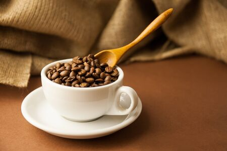 A white cup with coffee beans. A scattering of coffee beans with a cup. Coarse fabric.