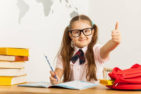 Happy little girl in glasses with opened notebook and school bag at the desk, showing thumb up sign. Education concept.