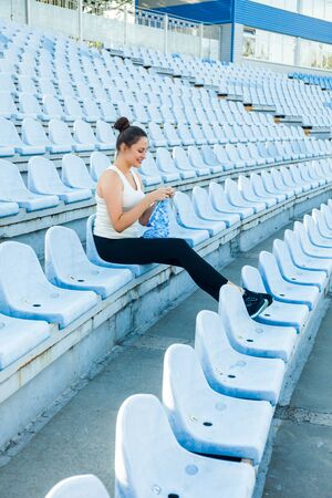 A young dark-haired woman in a sports suit at the empty stadium kniting a blue sweater. Get Creative everywhere 版權商用圖片