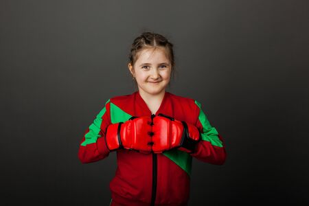 Beautiful little girl boxer in gloves ready to fight.