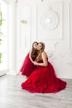 Mother and daughter in same outfits posing in the interior of the photo studio weared Red Dresses. Family look