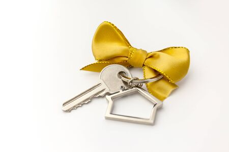House key with red bow on white background