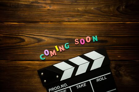 Coming soon Word made from multi-colored wooden letters on a brown wooden background and movie clapperboard. Filmmaking concept