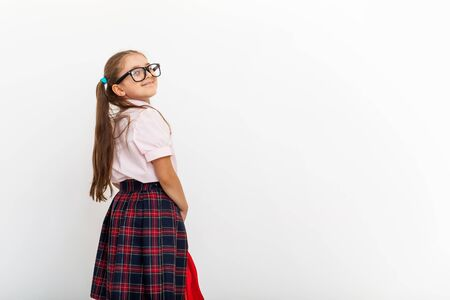 Full length portrait of smiling schoolgirl in uniform and eye glasses, holding red backpack standing on white background