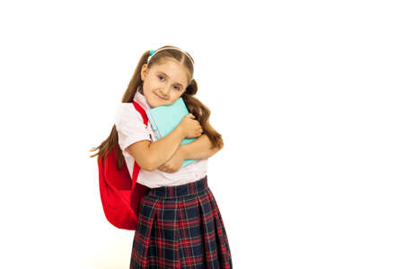 Portrait of a schoolgirl in uniform with backpack hugs a book isolated on white background.