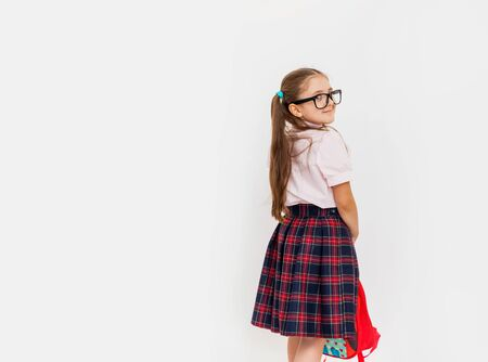 Full length portrait of smiling schoolgirl in uniform and eye glasses, holding red backpack standing on white background with copy space for text Foto de archivo