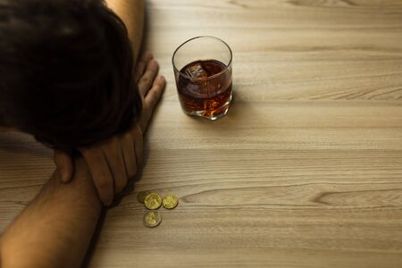 Depressed man, drunk, sleeping on the table, with a glass of cognac in hand, Bottle and last coins. Poverty, alcoholism and depression concept