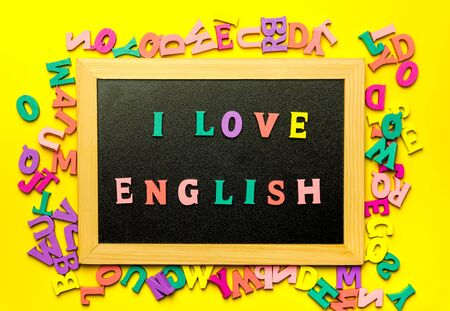 I love English word made with wooden letters on the Blackboard surface composition on Yellow background. Learning a foreign language concept