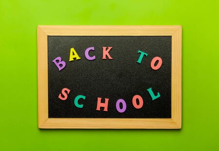 Phrase Back to school text colorful letters on blackboard, on green Backgound. School, education concept. Foto de archivo