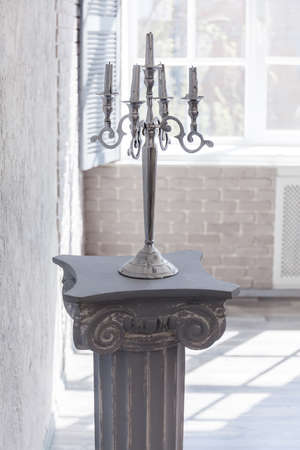 antique column and candlestick with five candles in abstract interior Zdjęcie Seryjne