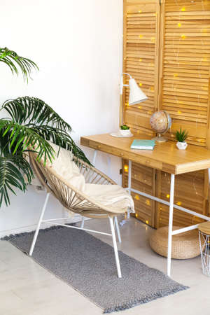 Cozy Workplace with table, rattan chair, white lamp in living room