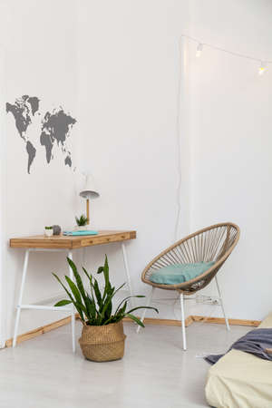 Bright workspace in white and wood in scandi style. Stylish table with lamp and notebook, modern rattan chair, world map on a white wall