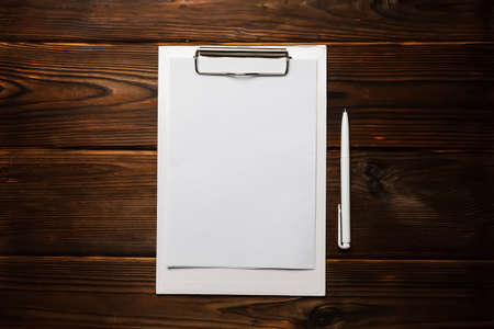 White clipboard with blank sheet of paper and white pen on wooden background. Top view office accessories concepts