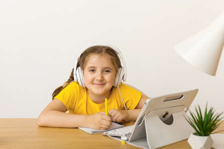 Caucasian Little girl in headphones sit at desk writing in notebook studying online at home, little child handwrite prepare homework on quarantine, have web lesson indoors. Covid-19 coronavirus.