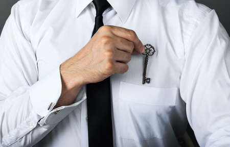 Trade secret concept. Close-up, businessman hides success key in shirt pocket 스톡 콘텐츠