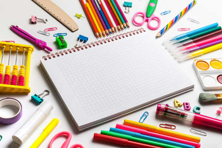 School office supplies on a desk with copy space. Back to school concept. Blank notebook with colourful school supplies