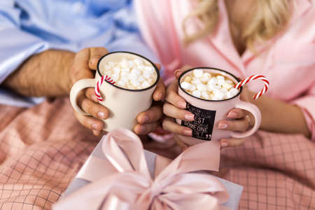 Couple hands with cups of hot chocolate with marshmallow close up image, cozy morning home at christmas time