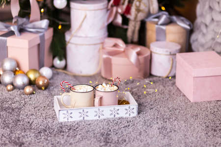 Tray with two cups of cocoa with marshmallows on a gray fluffy carpet, against the background of a Christmas tree, many gifts and New Year's decor Stock Photo
