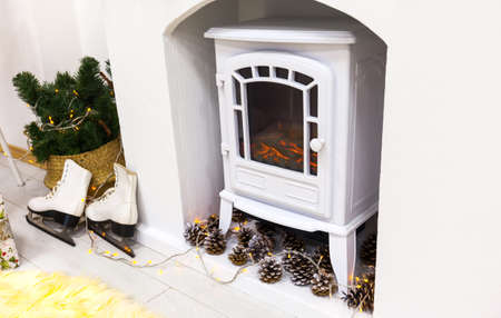 christmas mood, close-up of electric retro fireplace and white skates, holiday decor Stock Photo