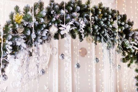 Decorative arch made of spruce branches, decorated with stylish baubles and balls, against the background of a white wall, in the interior