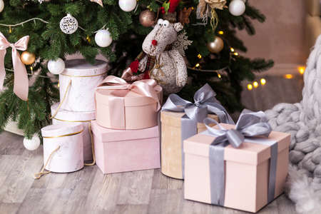 Decorated Christmas tree with baubles and tinsel surrounded by Pink and beige with RIBBONS gift wrapped presents and Santa toy reindeer in living room.