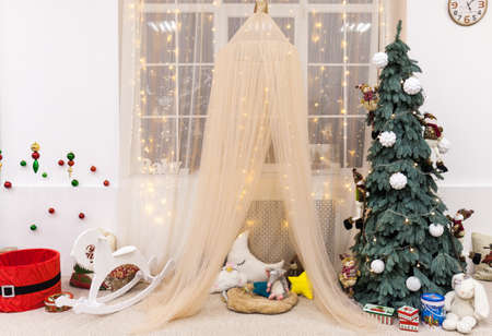 Modern interior design children's room with a large window with Christmas and New Year decorations, tent, toys, gifts, tree, rocking horse. Winter holidays composition.