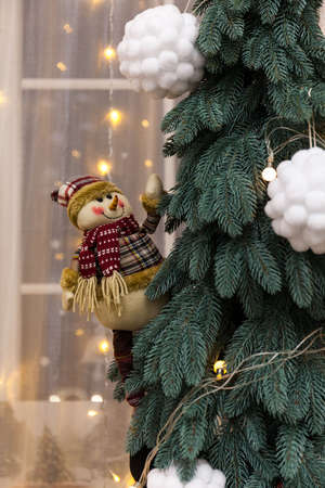 Christmas Decorations with A toy snowman in a hat and scarf hanging on the Christmas tree, lithts and white balls snowballs