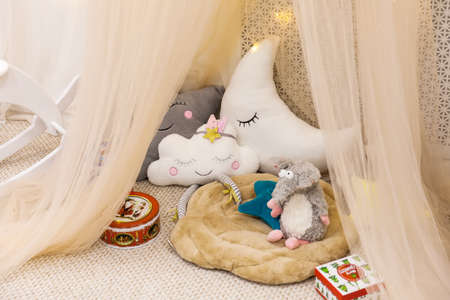 Children's room in pastel colors with fabric tent, toys, pillows and Christmas gifts and lights