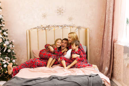 Happy family hug, having fun at Christmas time. Father, mother and childrens in red plaid pajamas in bedroom. Xmas holiday concept Stock Photo