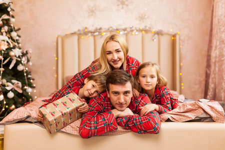 Closeup portrait of cute cheerful family in red plaid pajamas lying down near Christmas tree at home, happy parents with two kids celebrate New Year holiday, love concept Stock Photo
