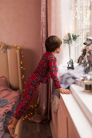 Cute Curious boy in plaid pajama, looking through a window, waiting impatiently for Santa and gifts Stock Photo