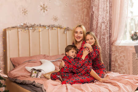 Happy children hug mom and smiling. Happy family in red plaid pajamas in the bedroom in Christmas morning Stock Photo