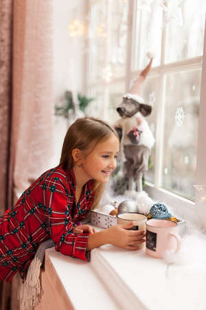 Cute Happy girl in plaid pajama with cup of cocoa, looking through a window and smiling, waiting impatiently for Christmas Stock Photo