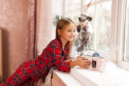 Cute Happy girl in plaid pajama with cup of cocoa, looking through a window, waiting impatiently for Christmas