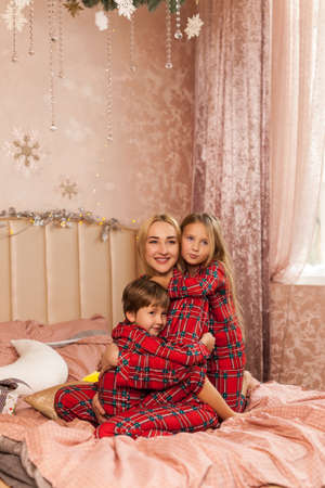 Happy children hug mom and smiling. Happy family in red pajamas in the bedroom in Christmas morning