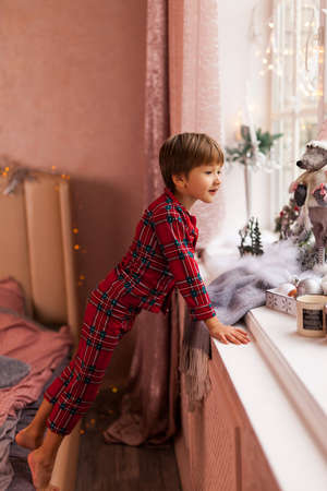 Cute Happy boy in plaid pajama, Stands on the edge of the bed reaching for the window to look through a window, waiting impatiently for Santa and gifts