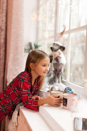 Cute Happy girl with cup of cocoa, looking through a window
